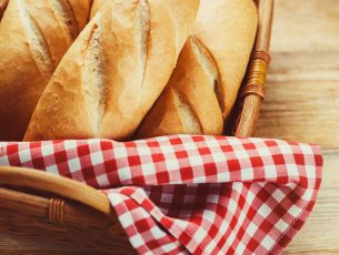 Fresh bread in  basket on a wooden table