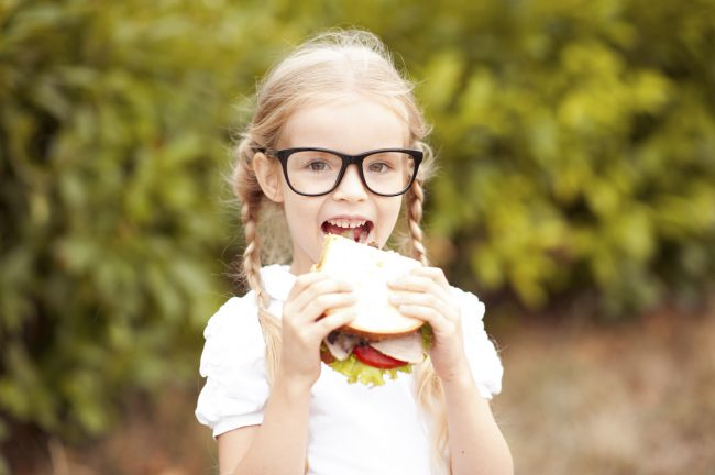 Portrait of cute kid girl 6-7 year old eating sandwich outdoors. Childhood. Healthy lifestyle. Looking at camera.